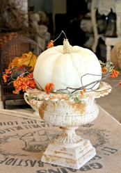 a vintage urn with blooming branches and a large white pumpkin is a chic fall decoration for outdoors