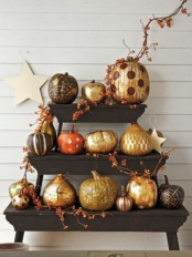 a stand with pumpkins and gourds paitned in various ways, in black and gold for fall and Halloween looks fantastic
