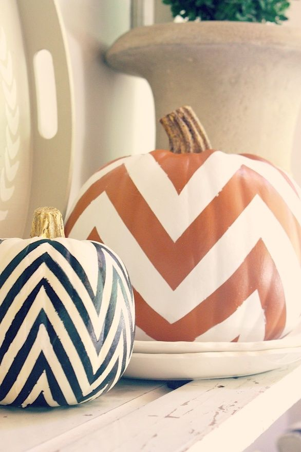 two pumpkins with orange, black and white chevrons can decorate any mantel in a stylish mid century modern way