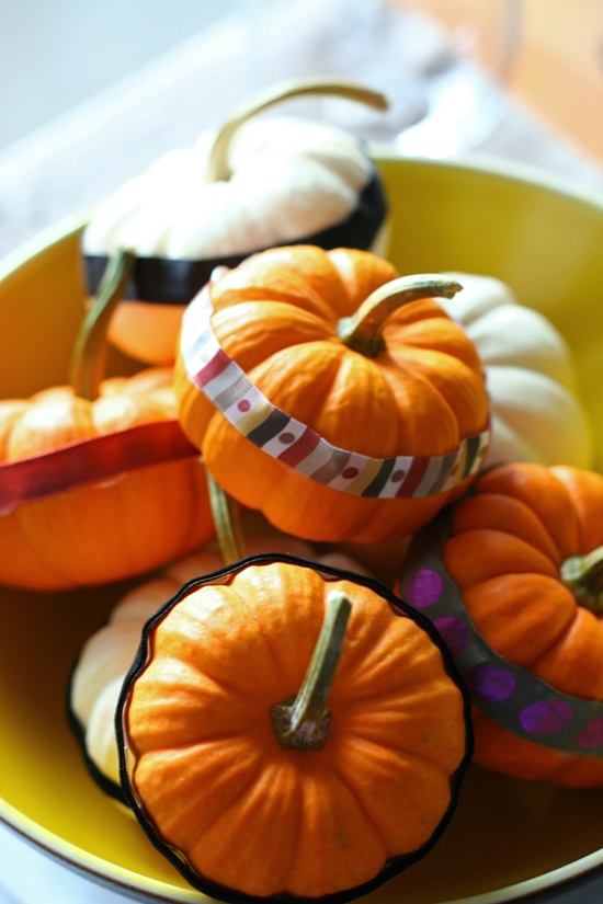 decorate pumpkins with colorful stripes of paper and fabric to create a bright and natural fall centerpiece
