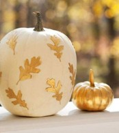 a pumpkin painted gold and a white pumpkin with gold leaves on it are cool and chic fall decorations