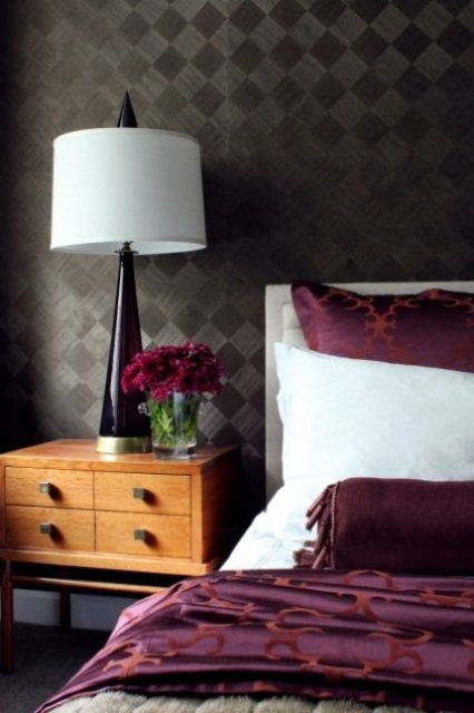 a purple table lamp and bedding are nice accents for this dramatic bedroom, and blooms match, too