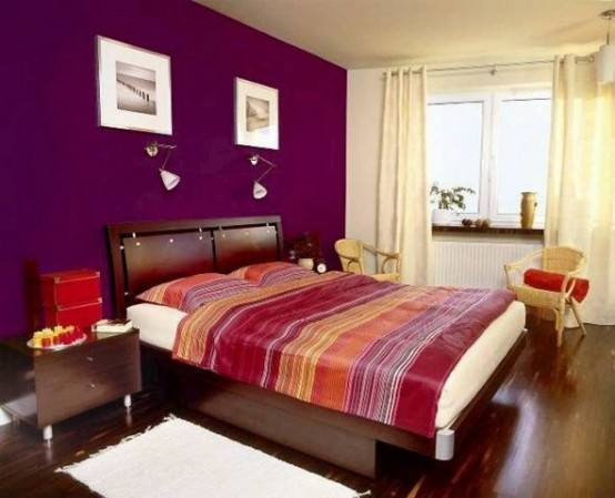 a colorful bedroom with a purple accent wall, dark stained furniture, bright bedding, sconces and artworks is a perfect warm-colored bedroom