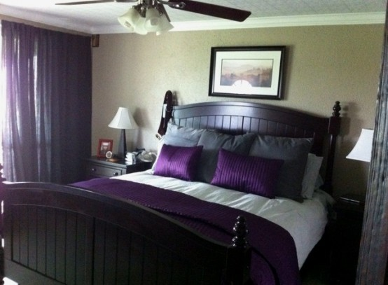 a welcoming bedroom with tan walls, dark stained furniture, grey and purple bedding and purple curtains makes a color statement