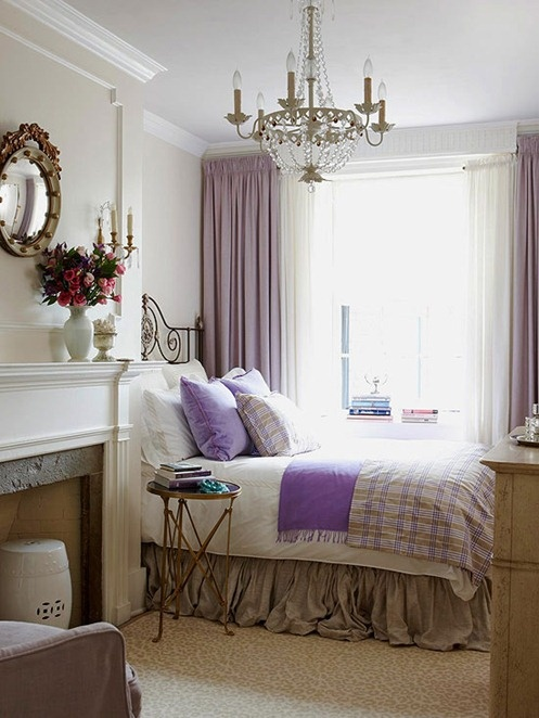 a French country bedroom with a non-working fireplace, a forged bed, some plaid and lavender bedding, a crystal chandelier and a mirror