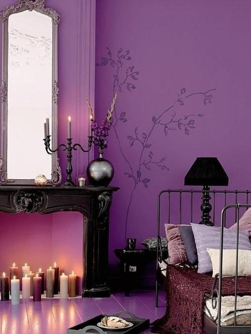 a purple bedroom with a black fireplace, a vintage mirror, some candles, a metal bed, a black lamp and some purple bedding is very romantic