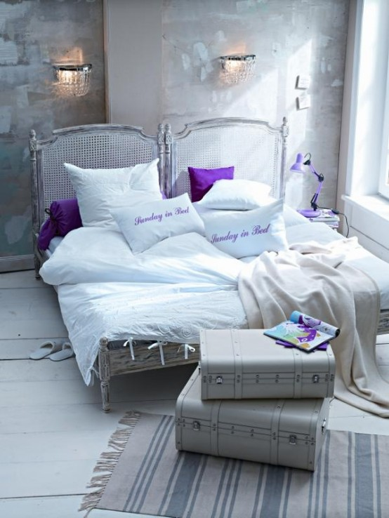 a whitewashed bedroom with brushstrokes on the wall, a whitewashed rattan bed, suitcases and some white and purple bedding