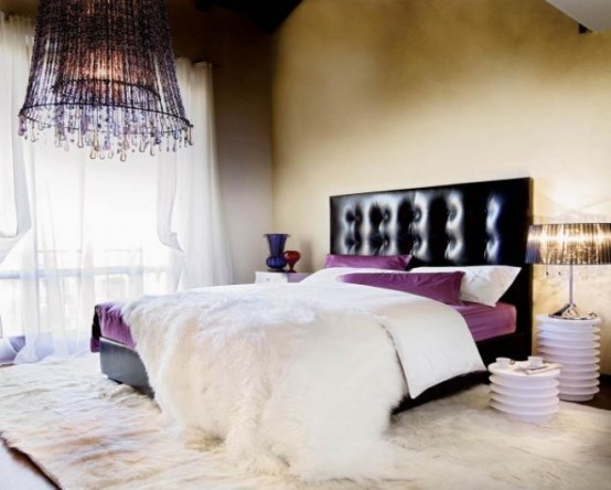 a tan bedroom with a black upholstered bed, purple and white bedding, table lamps and a purple crystal chandelier for colorful accents