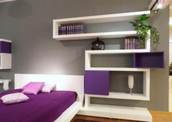 a minimalist white and purple bedroom with a bed, a shelving unit, some greenery and lights is a stylish space with nothing excessive