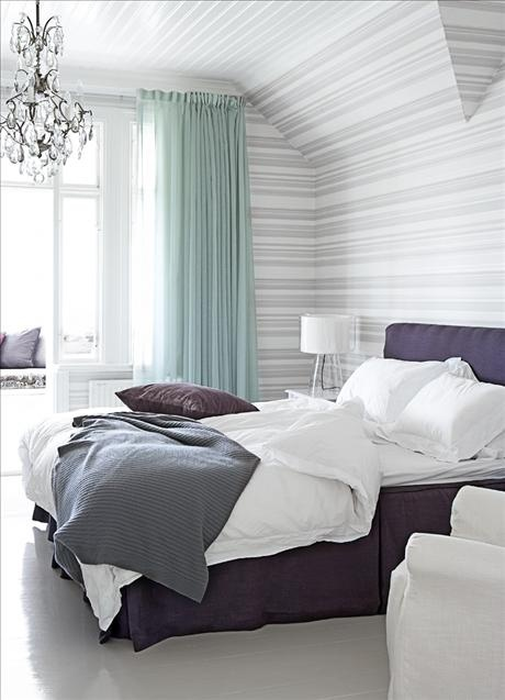 a striped bedroom with aqua curtains, a crystal chandelier and a purple upholstered bed plus purple pillows for a color statement