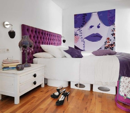 a white bedroom with a purple bed, purple pillows and an artwork, a vintage table lamp with crystals and some storage boxes