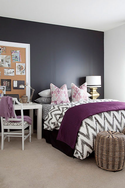 a black and white bedroom with a black bed, woven baskets for storage, white furniture, a board for memos and table lamps