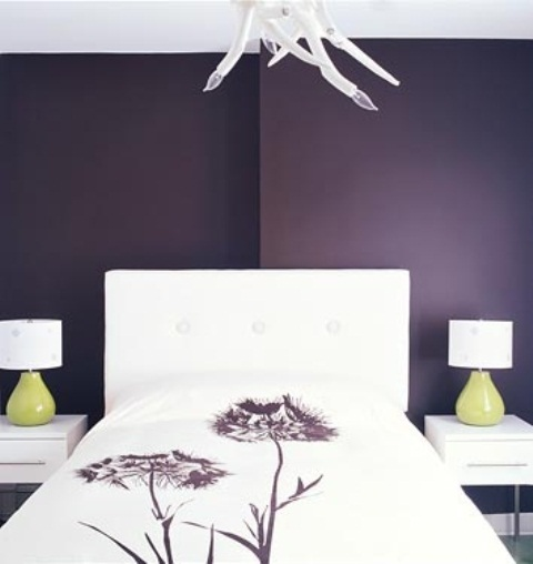 a purple bedroom with white furniture, table lamps with green bases and a quirky chandelier looks unique and statement-like