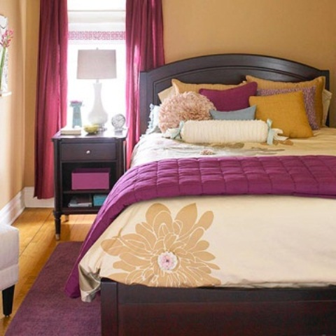 a buttermilk bedroom with dark stained furniture, with purple touches and textiles and buttermilk pillows feels welcoming