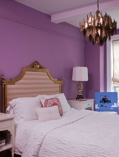 a purple bedroom with a refined bed, a unique copper chandelier, table lamps and neutral bedding looks whimsical
