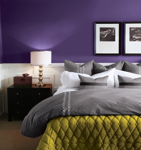 a bold purple bedroom with white paneling, grey and white bedding, a mustard blanket, dark stained furniture and chic artworks