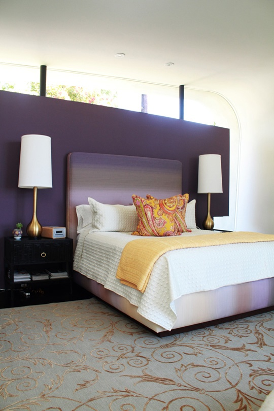 a deep purple accent wall, black nightstands, table lamps with gold bases, an ombre bed and bright bedding