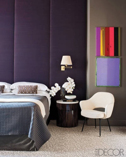 a purple and tan bedroom with a black bed, a dark stained nightstand, colorful artworks and a neutral chair is very refined and chic