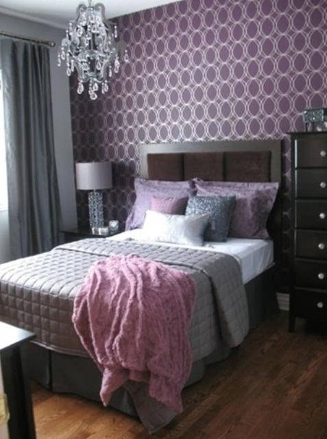a stylish and refined bedroom with purple printed wallpaper, dark furniture, a crystal chandelier, grey and purple bedding and a wooden floor