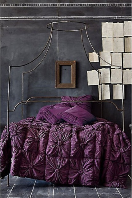 a moody bedroom with chalkboard walls, a forged bed, deep purple bedding and pages of the book attached right to the wall