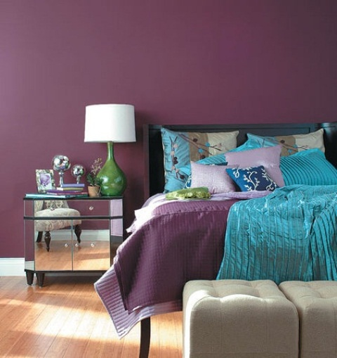 a purple bedroom with a black bed, neutral ottomans, mirror nightstands, table lamps with green bases and shiny accessories here and there
