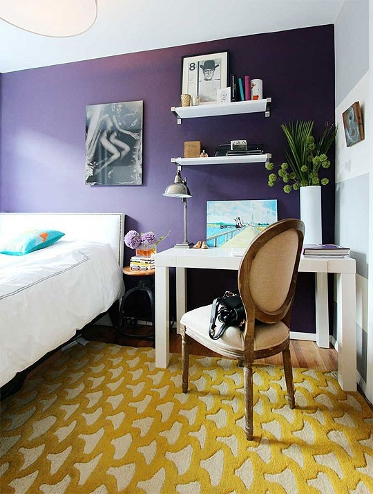 a colorful bedroom with a deep purple accent wall, white furniture, an artwork and a bold carpet on the floor just wows