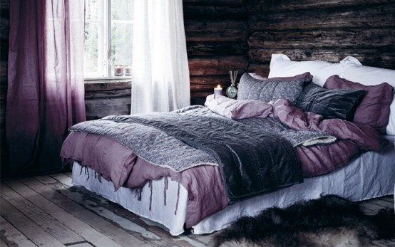 a rough wooden bedroom with white and purple bedding and curtains is a fresh take on a classic chalet bedroom