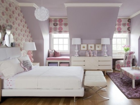 a lavender bedroom with a floral accent wall and curtains, white furniture and pink and lavender textiles here and there