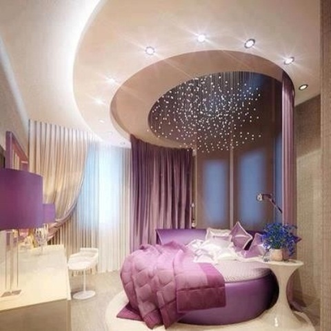 a warm tan and purple bedroom with a round bed, a rounded ceiling with lights, purple bedding and table lamps