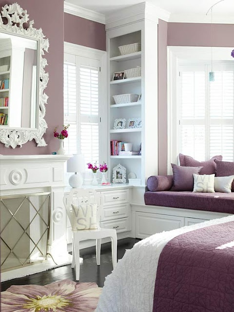 a purple and white bedroom with purple walls and vintage white furniture plus a non-working fireplace