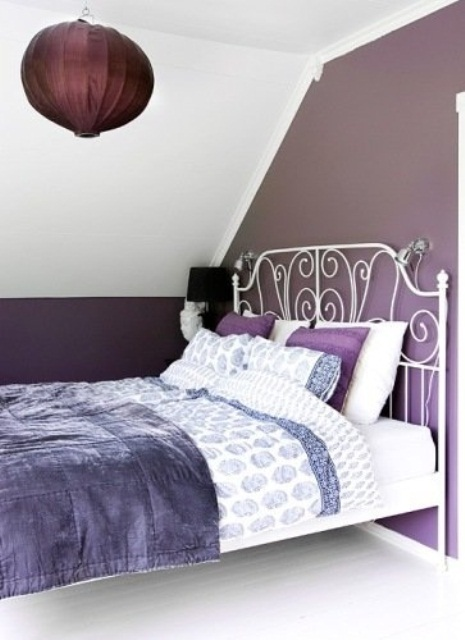 a small attic bedroom with a white forged bed, a purple paper lamp over the bed and purple and white bedding is cozy