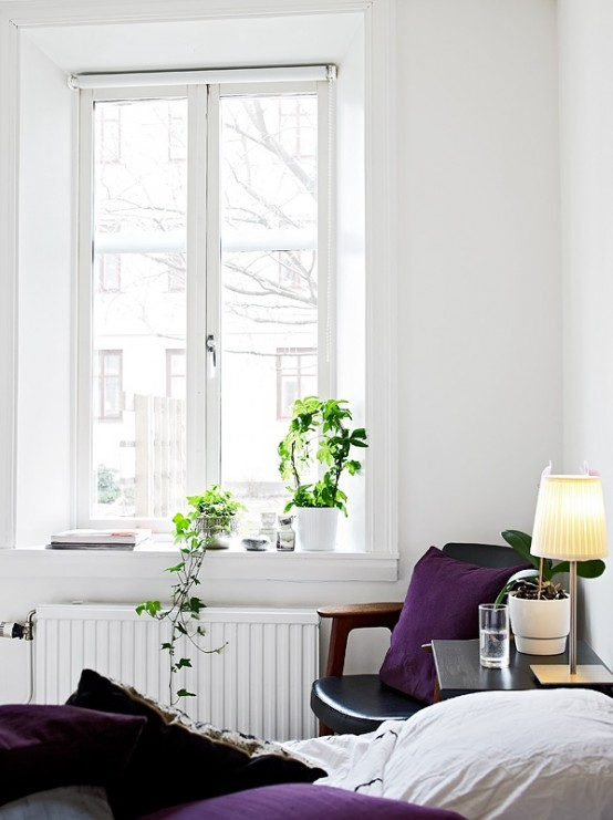 a neutral Scandinavian bedroom with a black leather chair, purple bedding and some potted plants and a table lamp