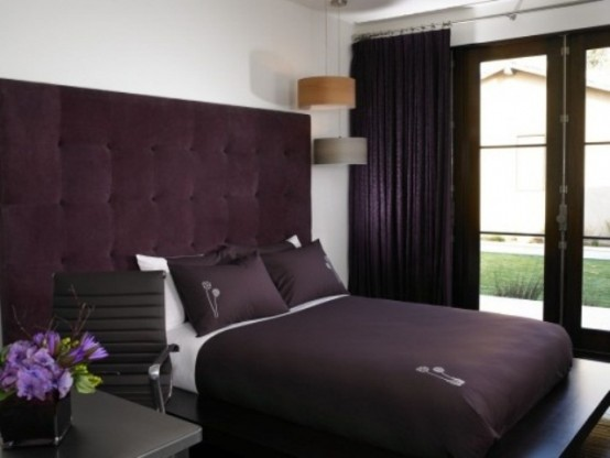 a contrasting deep purple and white bedroom with an upholstered headboard and deep purple textiles plus dark stained furniture is very elegant and laconic