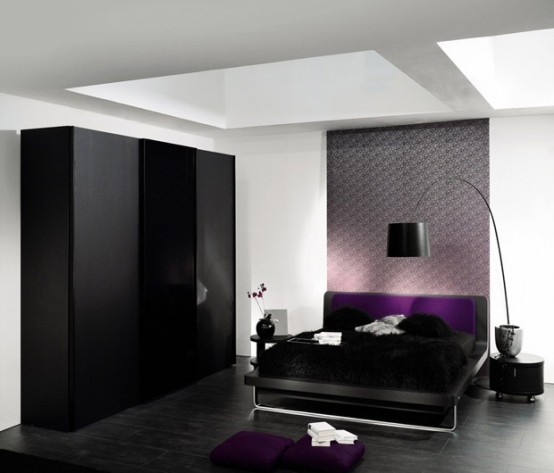 a bold bedroom with black furniture and a lamp, skylights and some purple textiles to add color to this space