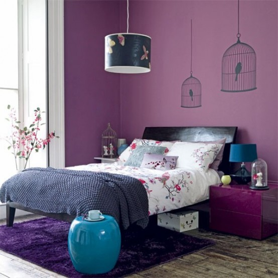 a purple bedroom with cage decals, a black bed, a purple nightstand, a bold butterfly lamp and some bright blue touches