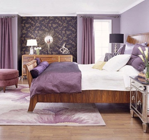 purple and lavender bedroom with printed wallpaper, stained wooden furniture, table lamps, a sunburst mirror and some purple textiles