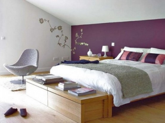 an attic bedroom with light-stained furniture and a grey chair, with purple and white bedding and some floral decor