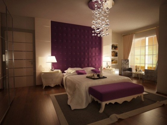 a neutral bedroom with a purple upholstered wall, purple pillows and a bench plus a bubble chandelier accenting the ceiling