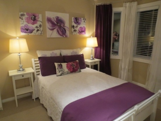 a tan bedroom with white furniture, purple floral artworks and pillows, purple curtains and bedding is a stylish and cool space