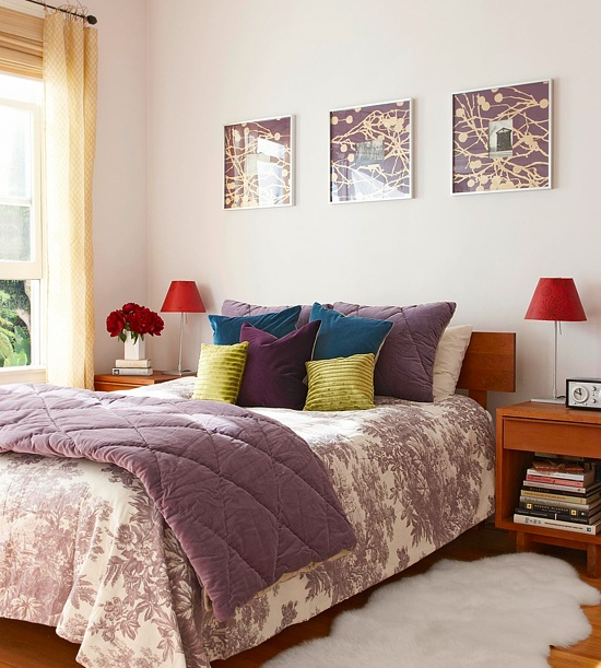 a colorful bedroom with mid-century modern wooden furniture, bright bedding and pillows, purple bedding and artworks