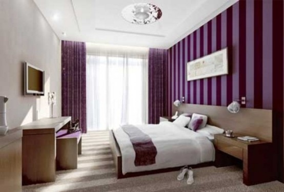 a purple and white bedroom with a striped purple wall and curtains, wooden furniture, a TV and a shiny chandelier is a contemporary bedroom