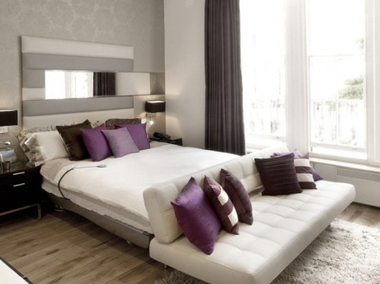 a monochromatic bedroom in grey and white, with cozy upholstered furniture, purple and white pillows, purple curtains for a touch of color