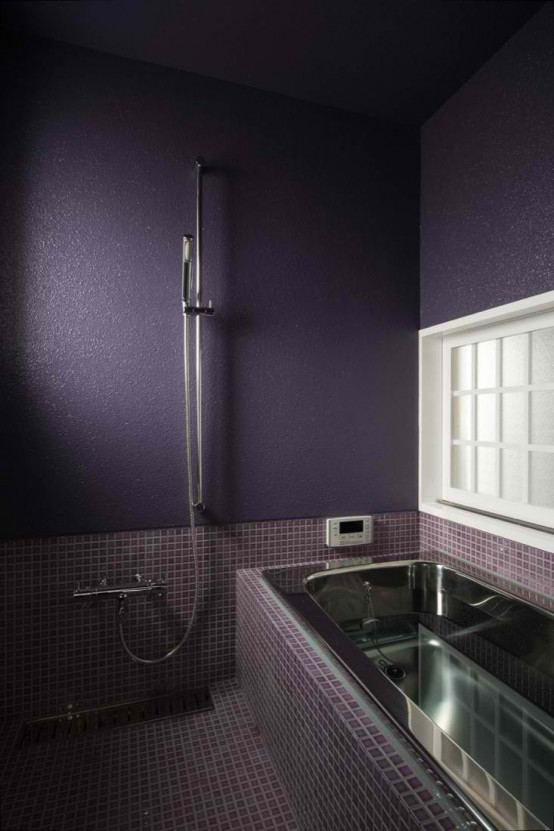a moody bathroom done in deep purple, matte purple walls, fuchsia and purple tiles and a metal bathtub