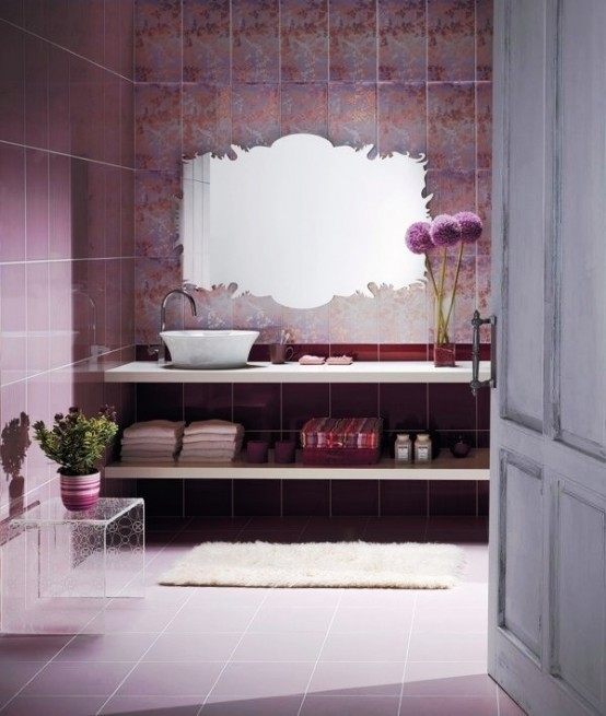 a whimsy purple bathroom with printed tiles, a chic cutout mirror, a floating vanity of shelves and an acrylic table