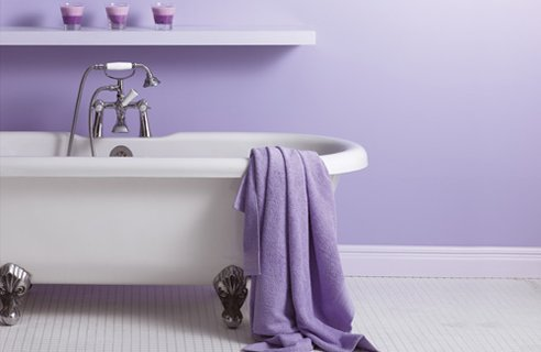 a cozy lavender infused bathroom with a white vintage tub and a white tile floor
