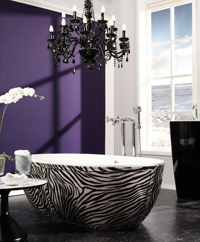 an exotic purple bathroom with a statement wall, a zebra print bathtub, a refined black chandelier and a black free-standing sink