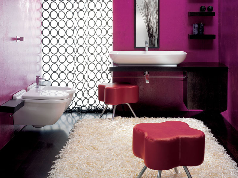 a bright contemporary space done with fuchsia, purple, black and white, leather poufs, a printed curtain and black furniture