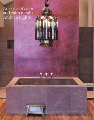 a Moroccan style bathroom done with purple tiles and bathtub plus a statement lantern