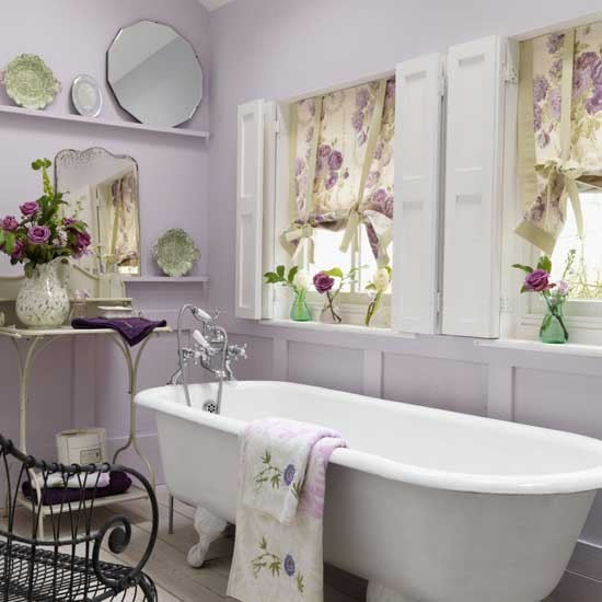 a girlish bathroom with lavender walls, a white vintage bathtub, florla curtains, exquisite mirrors and a forged table