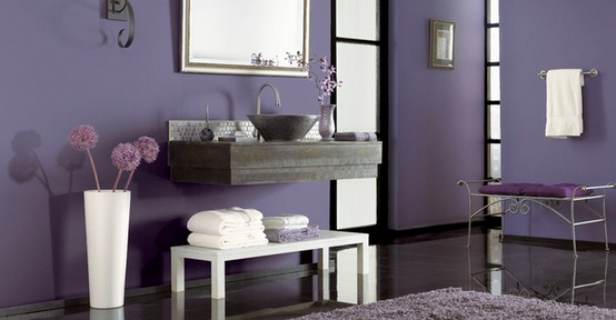 an eye catchy purple bathroom with a dark tile floor, a floating wooden vanity and metallic touches